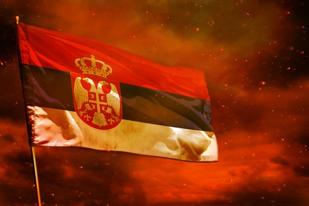 Fluttering Serbia flag on crimson red sky with smoke pillars background. Serbia problems concept. Stock fotó