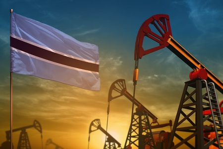 Botswana oil industry concept, industrial illustration. Fluttering Botswana flag and oil wells on the blue and yellow sunset sky background - 3D illustration