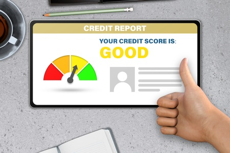 good credit score technology concept - hand with tablet computer shows like, thumb up   on stone table background Stock Photo