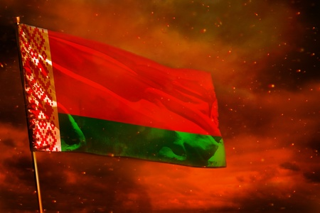Fluttering Belarus flag on crimson red sky with smoke pillars background. Belarus problems concept.