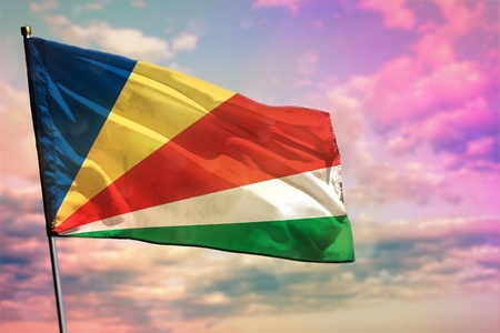 Fluttering Seychelles flag on colorful cloudy sky background. Seychelles prospering concept.