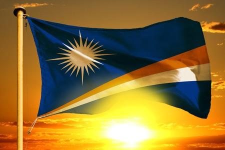 Marshall Islands flag weaving on the beautiful orange sunset background