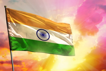 Fluttering India flag on beautiful colorful sunset or sunrise background. India success and happiness concept.