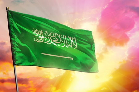 Fluttering Saudi Arabia flag on beautiful colorful sunset or sunrise background. Saudi Arabia success and happiness concept. 版權商用圖片