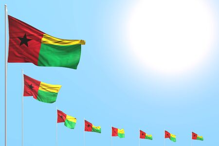 wonderful many Guinea-Bissau flags placed diagonal on blue sky with place for text - any feast flag 3d illustration 写真素材