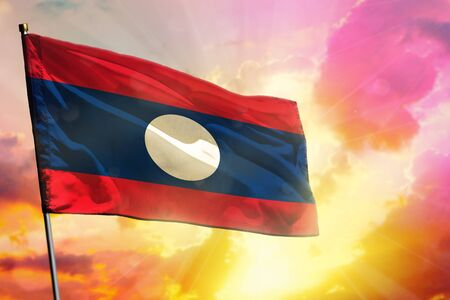 Fluttering Lao People Democratic Republic flag on beautiful colorful sunset or sunrise background. Lao People Democratic Republic success and happiness concept.