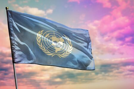 Fluttering United Nations flag on colorful cloudy sky background. United Nations prospering concept.