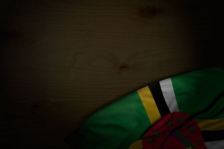 nice national holiday flag 3d illustration  - dark photo of Dominica flag with big folds on dark wood with free place for your text 版權商用圖片