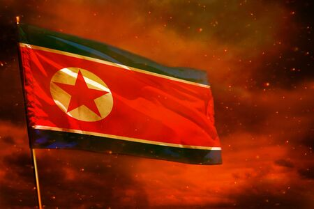 Fluttering Democratic Peoples Republic of Korea (North Korea) flag on crimson red sky with smoke pillars background. Democratic Peoples Republic of Korea (North Korea) problems concept.