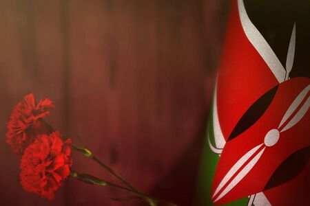 Kenya flag with two red carnation flowers for honour of veterans or memorial day on red blurred natural wood wall mockup. Kenya glory to the heroes of war concept. 스톡 콘텐츠