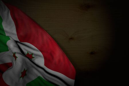 beautiful dark image of Burundi flag with large folds on dark wood with free space for your content - any celebration flag 3d illustration Stock Photo