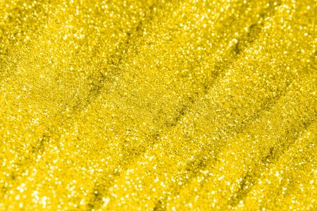 fantastic yellow brilliant sand made of golden glitters with selective focus and small bokeh texture - abstract photo background