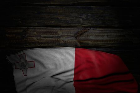 beautiful dark image of Malta flag with big folds on old wood with free place for text - any celebration flag 3d illustration 스톡 콘텐츠