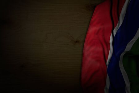 nice dark picture of Gambia flag with big folds on dark wood with empty place for your text - any feast flag 3d illustration