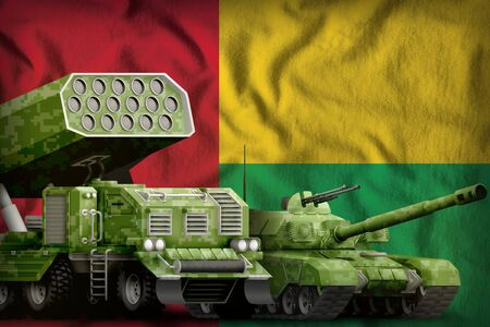 tank and missile launcher with summer pixel camouflage on the Guinea-Bissau flag background. Guinea-Bissau heavy military armored vehicles concept. 3d Illustration
