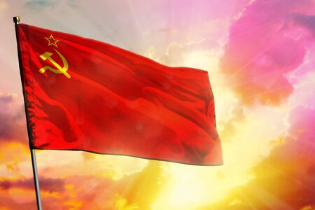 Fluttering Soviet Union (SSSR, USSR) flag on beautiful colorful sunset or sunrise background. Soviet Union (SSSR, USSR) success and happiness concept. Reklamní fotografie