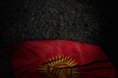 pretty dark image of Kyrgyzstan flag with large folds on dark asphalt with empty place for your content - any holiday flag 3d illustration