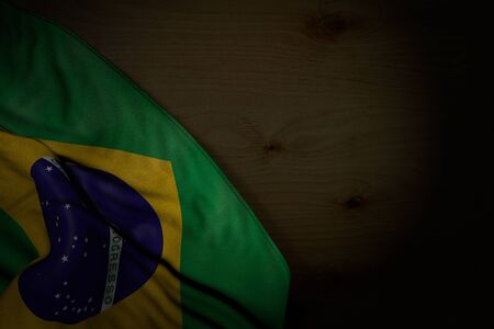 wonderful dark picture of Brazil flag with big folds on dark wood with empty space for text - any feast flag 3d illustration