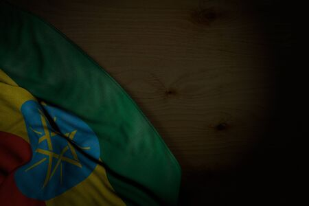 pretty dark photo of Ethiopia flag with big folds on dark wood with free place for text - any celebration flag 3d illustration  Banco de Imagens