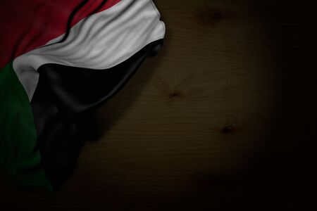 pretty dark photo of Sudan flag with large folds on dark wood with free place for text - any celebration flag 3d illustration