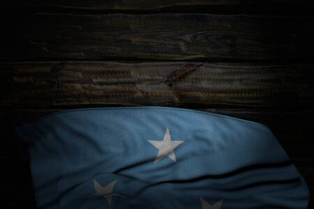 beautiful dark photo of Micronesia flag with big folds on old wood with empty place for your content - any occasion flag 3d illustration