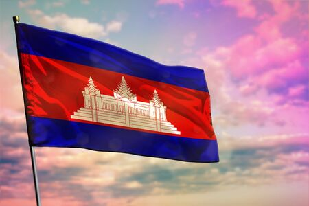 Fluttering Cambodia flag on colorful cloudy sky background. Cambodia prospering concept.