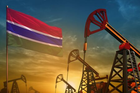 Gambia oil industry concept, industrial illustration. Fluttering Gambia flag and oil wells on the blue and yellow sunset sky background - 3D illustration Zdjęcie Seryjne