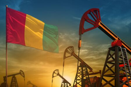 Guinea oil industry concept, industrial illustration. Fluttering Guinea flag and oil wells on the blue and yellow sunset sky background - 3D illustration