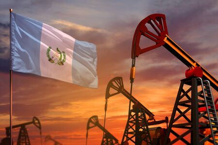 Guatemala oil industry concept, industrial illustration. Guatemala flag and oil wells and the red and blue sunset or sunrise sky background - 3D illustration