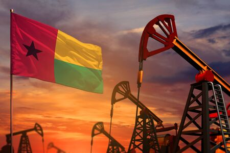 Guinea-Bissau oil industry concept, industrial illustration. Guinea-Bissau flag and oil wells and the red and blue sunset or sunrise sky background - 3D illustration