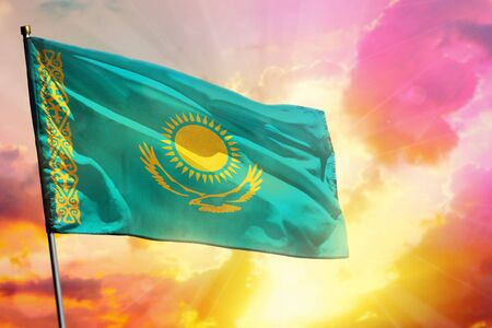 Fluttering Kazakhstan flag on beautiful colorful sunset or sunrise background. Kazakhstan success and happiness concept.
