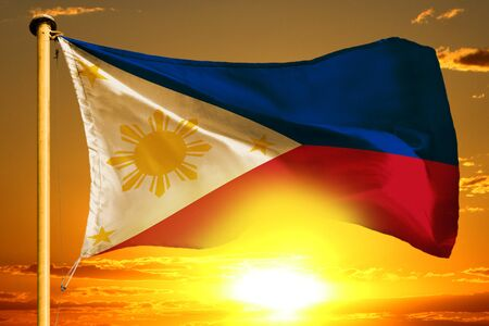 Philippines flag weaving on the beautiful orange sunset background 写真素材