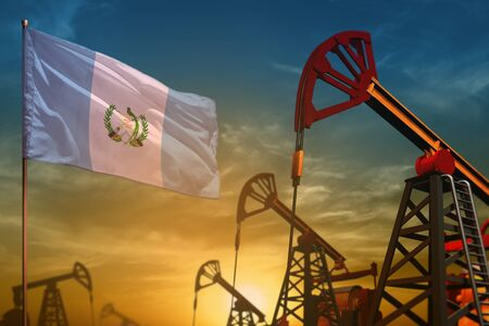 Guatemala oil industry concept, industrial illustration. Fluttering Guatemala flag and oil wells on the blue and yellow sunset sky background - 3D illustration