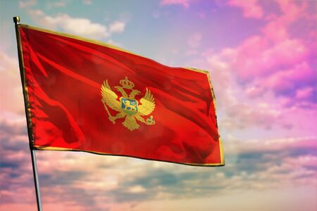 Fluttering Montenegro flag on colorful cloudy sky background. Montenegro prospering concept.