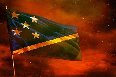Fluttering Solomon Islands flag on crimson red sky with smoke pillars background. Solomon Islands problems concept. Stock fotó