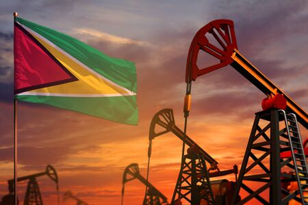 Guyana oil industry concept, industrial illustration. Guyana flag and oil wells and the red and blue sunset or sunrise sky background - 3D illustration Imagens