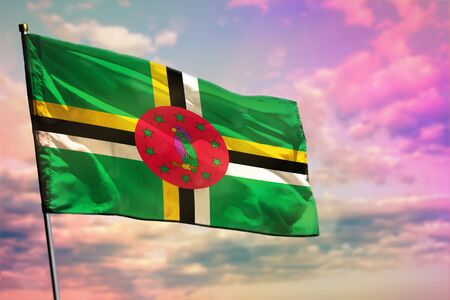 Fluttering Dominica flag on colorful cloudy sky background. Dominica prospering concept.