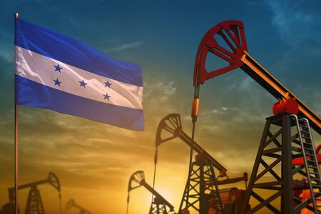 Honduras oil industry concept, industrial illustration. Fluttering Honduras flag and oil wells on the blue and yellow sunset sky background - 3D illustration Фото со стока