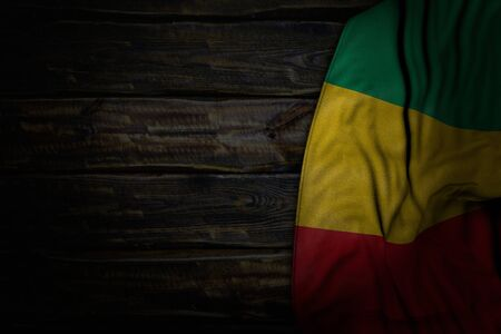 pretty dark image of Guinea flag with large folds on old wood with free place for content - any feast flag 3d illustration