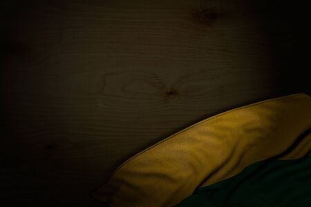 wonderful dark photo of Lithuania flag with large folds on dark wood with free place for your content - any feast flag 3d illustration