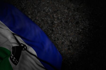 wonderful memorial day flag 3d illustration  - dark picture of Lesotho flag with large folds on dark asphalt with free place for your content