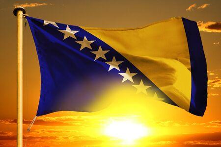 Bosnia and Herzegovina flag weaving on the beautiful orange sunset background