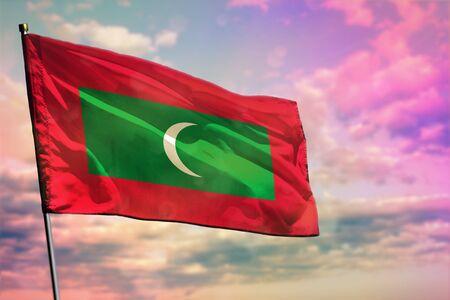 Fluttering Maldives flag on colorful cloudy sky background. Maldives prospering concept.