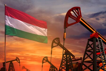 Hungary oil industry concept, industrial illustration. Hungary flag and oil wells and the red and blue sunset or sunrise sky background - 3D illustration