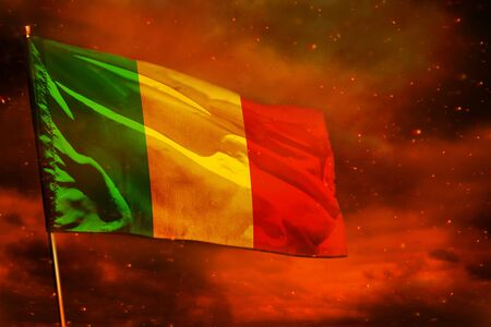 Fluttering Mali flag on crimson red sky with smoke pillars background. Mali problems concept.