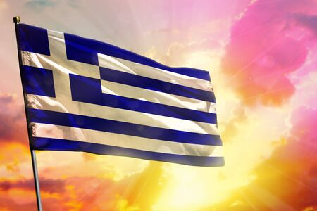Fluttering Greece flag on beautiful colorful sunset or sunrise background. Greece success and happiness concept. Imagens