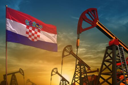 Croatia oil industry concept, industrial illustration. Fluttering Croatia flag and oil wells on the blue and yellow sunset sky background - 3D illustration Фото со стока