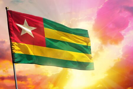 Fluttering Togo flag on beautiful colorful sunset or sunrise background. Togo success and happiness concept.