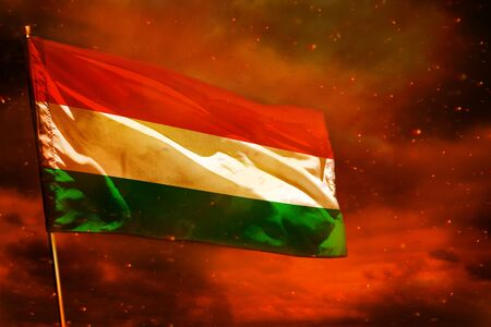 Fluttering Hungary flag on crimson red sky with smoke pillars background. Hungary problems concept. Фото со стока