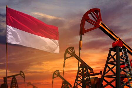 Indonesia oil industry concept, industrial illustration. Indonesia flag and oil wells and the red and blue sunset or sunrise sky background - 3D illustration Banco de Imagens